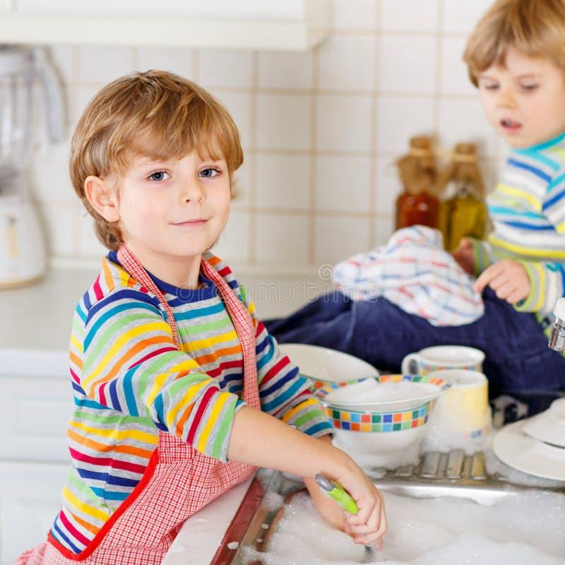 Kleiner lustiger Helfer zwei in der Küche mit waschenden Tellern stockfoto