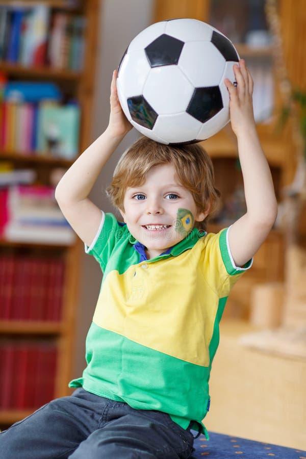 Kleiner lustiger Kinderjunge, der zu Hause mit einem Fußball spielt stockfotografie