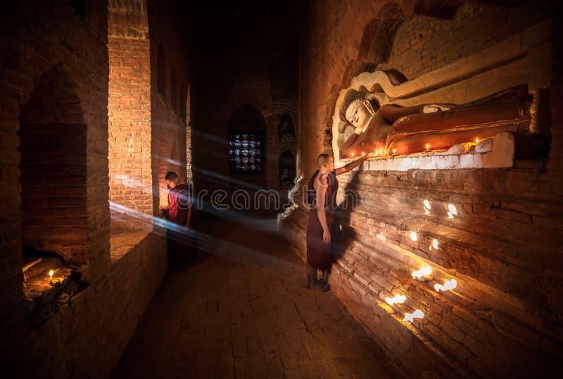 Kleiner Mönch, der mit Kerzen betet stockfotos