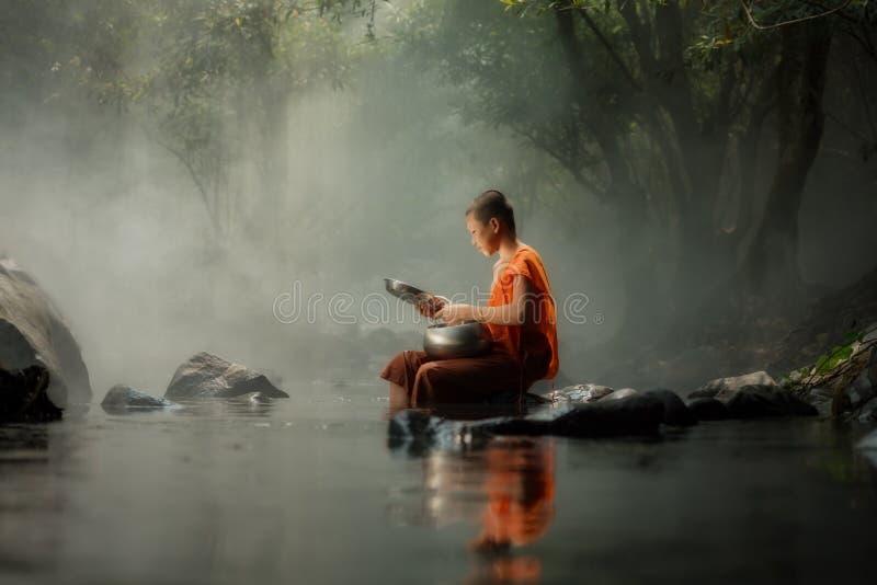 Kleiner Mönch Thailands, der auf The Creek oder Fluss im Wald an sitzt lizenzfreie stockbilder