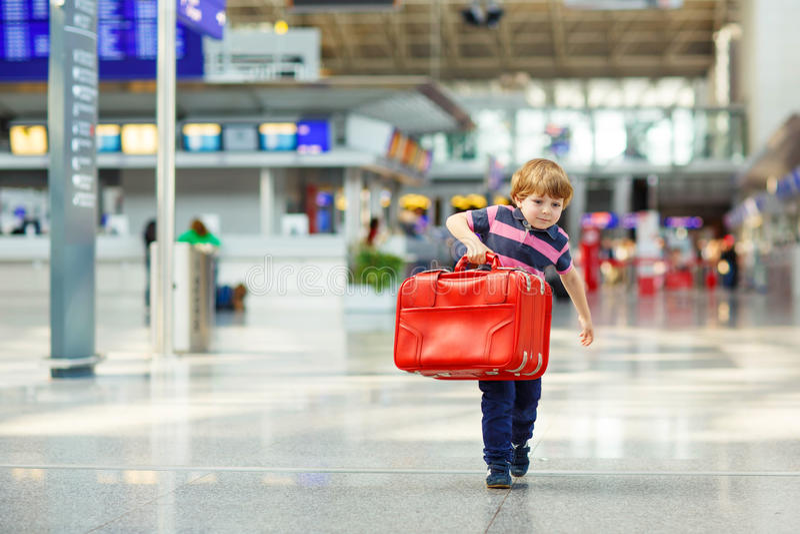 Kleiner müder Kinderjunge am Flughafen, reisend lizenzfreies stockbild