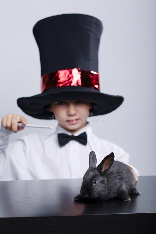 Kleiner Magier mit Kaninchenatelieraufnahme stockfotografie