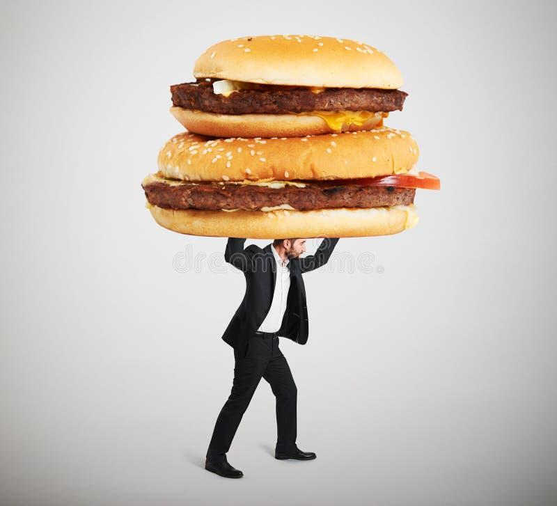 Kleiner Mann, der große Sandwiche trägt lizenzfreies stockfoto