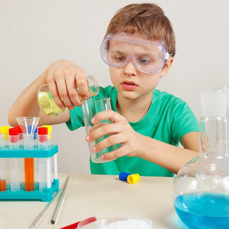 Kleiner nachdenklicher Junge in den Sicherheitsschutzbrillen, die chemische Experimente im Labor tun stockfotografie