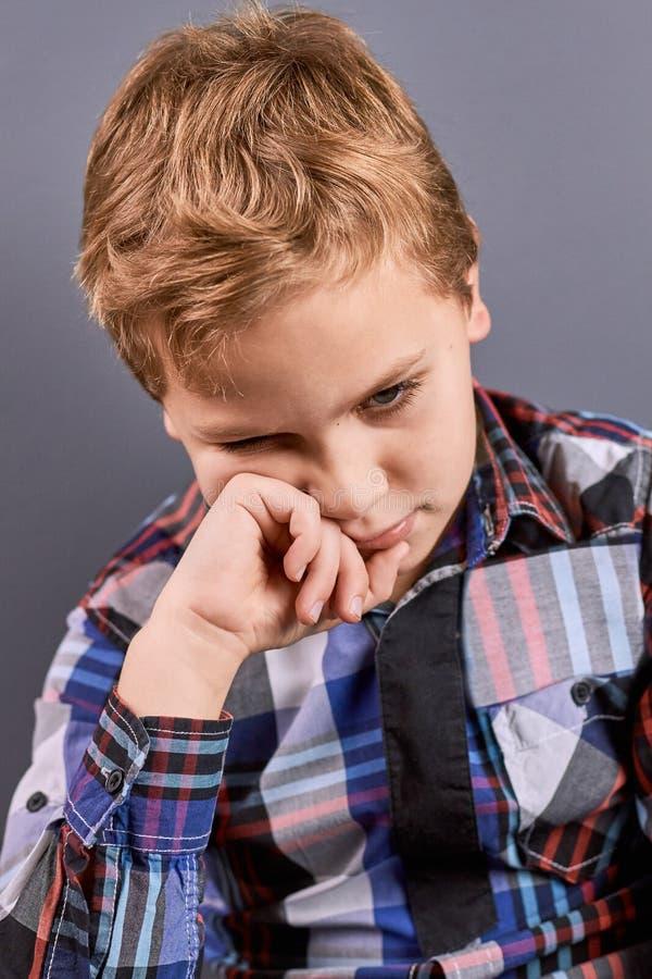 Kleiner nachdenklicher Junge, der unten schaut lizenzfreie stockfotografie