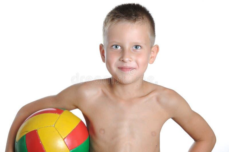 Kleiner netter Junge, der den Fußballball lokalisiert spielt stockbild