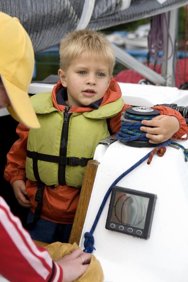 Kleiner netter Junge in der Schwimmweste auf Yacht. lizenzfreie stockfotos