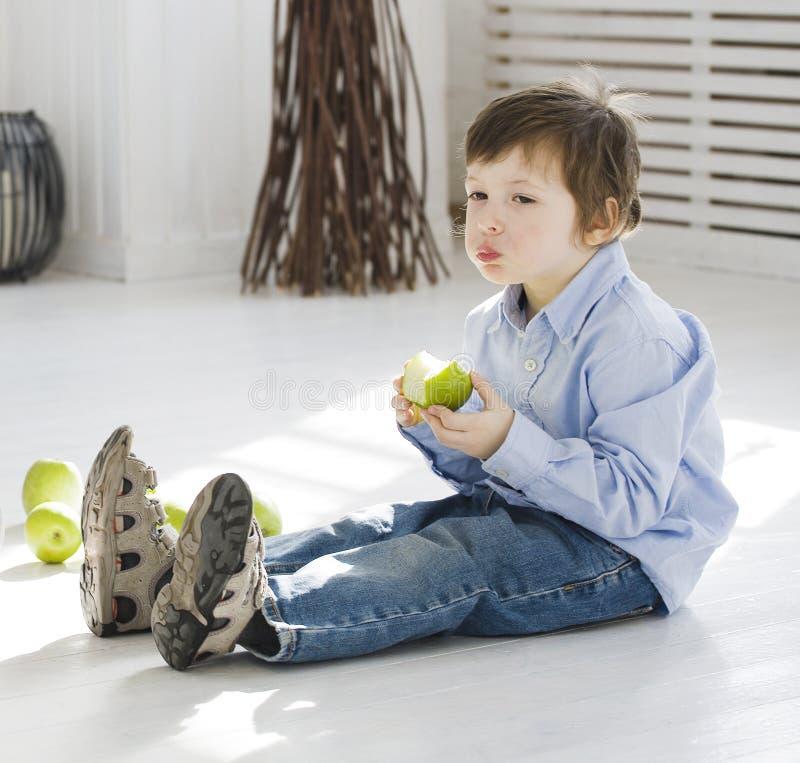 Kleiner netter Junge, der zu Hause grünen Apfel isst stockfotos