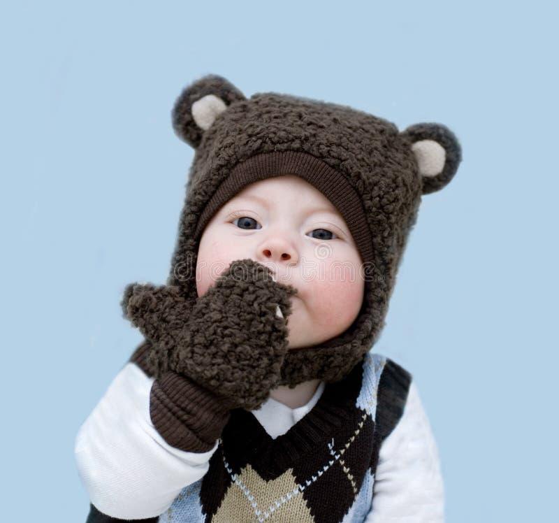 Kleiner netter kleiner Junge in einem Teddybärkostüm auf einem blauen Hintergrund sendet einen Kuss stockbilder
