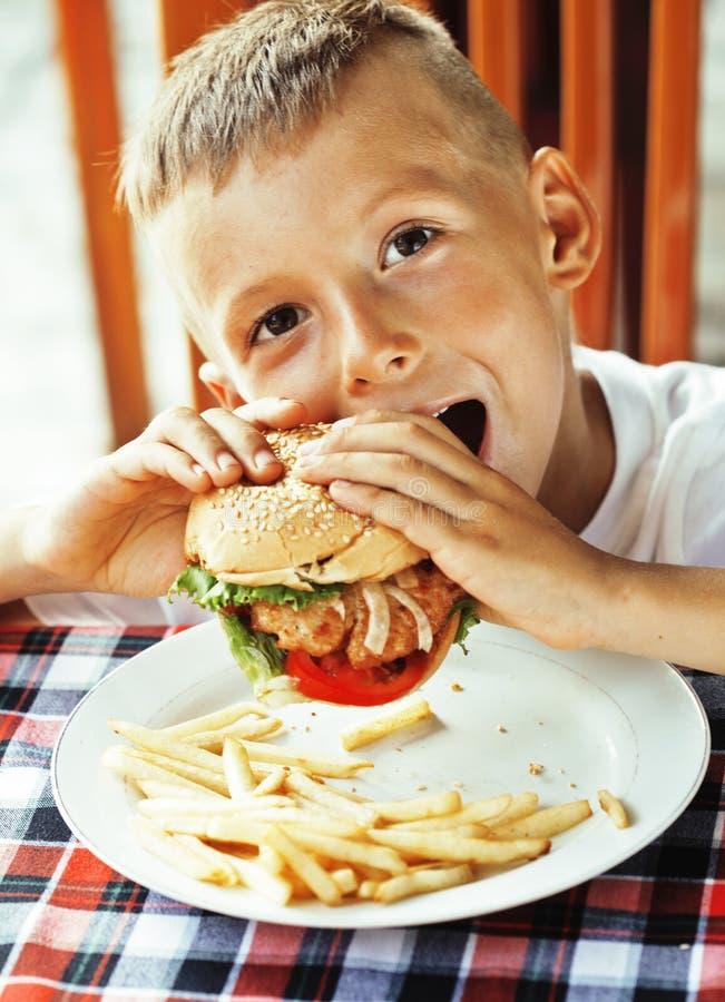 Kleiner netter Junge 6 Jahre alt mit Hamburger und Pommes-Frites maki lizenzfreie stockbilder