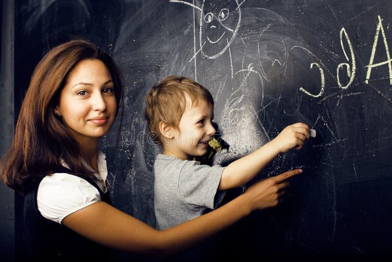 Kleiner netter Junge mit dem jungen Lehrer im Klassenzimmer studierend an der Tafel lächelnd, Lebensstilleutekonzept lizenzfreie stockfotografie