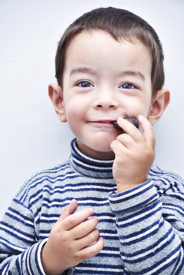 Kleiner netter Junge mit einem Gegenstand im Mund lizenzfreie stockfotografie