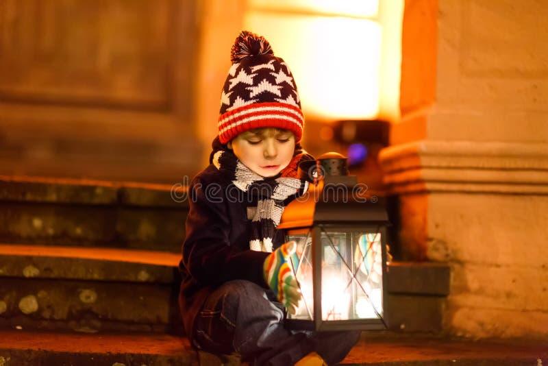 Kleiner netter Kinderjunge mit mit einer hellen Laterne auf Treppe nähern sich Kirche Glückliches Kind auf Weihnachtsmarkt in Deu lizenzfreie stockfotografie
