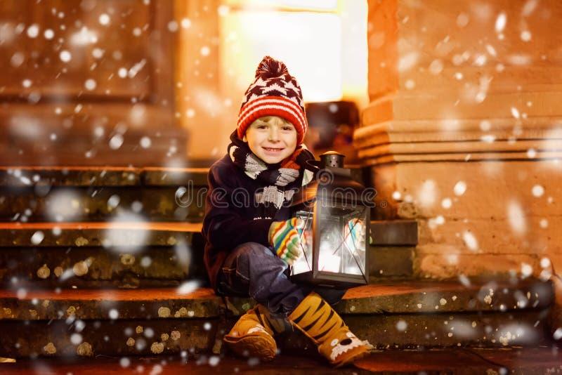 Kleiner netter Kinderjunge mit mit einer hellen Laterne auf Treppe nähern sich Kirche Glückliches Kind auf Weihnachtsmarkt in Deu lizenzfreies stockbild