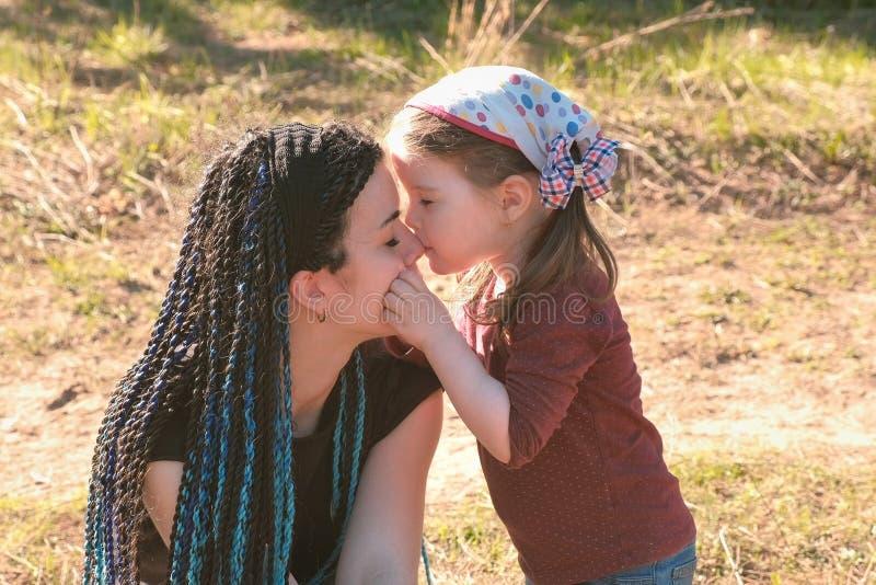 Kleiner netter Mädchenkuß und umarmen ihre Mutter Weg im Park lizenzfreie stockfotografie