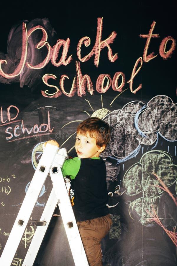 Kleiner netter wirklicher Junge an der Tafel im Klassenzimmer, zurück zu Schulkonzept lizenzfreie stockbilder