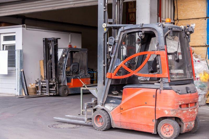 Kleiner orange Gabelstapler geparkt an einem Lager lizenzfreies stockbild