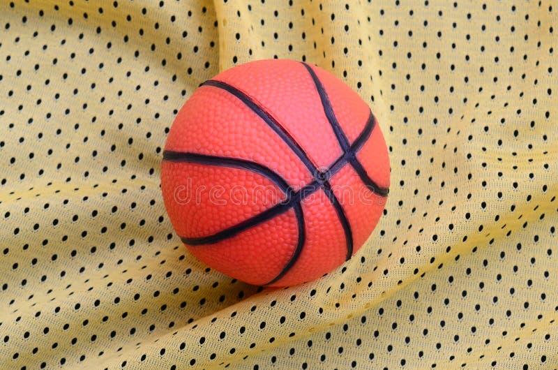 Kleiner orange Gummibasketball liegt auf einem gelben Sporttrikot Clo lizenzfreie stockfotos