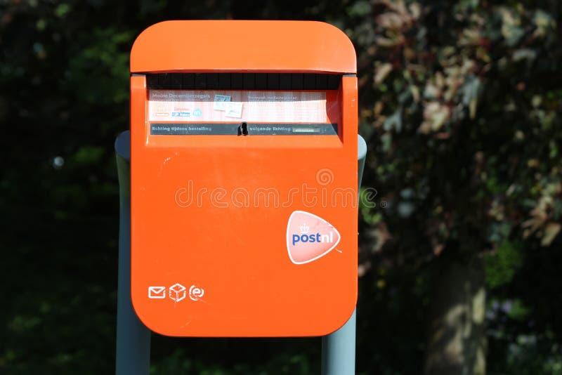 Kleiner orangefarbener Briefkasten von PostNl auf dem Land der Niederlande stockbilder