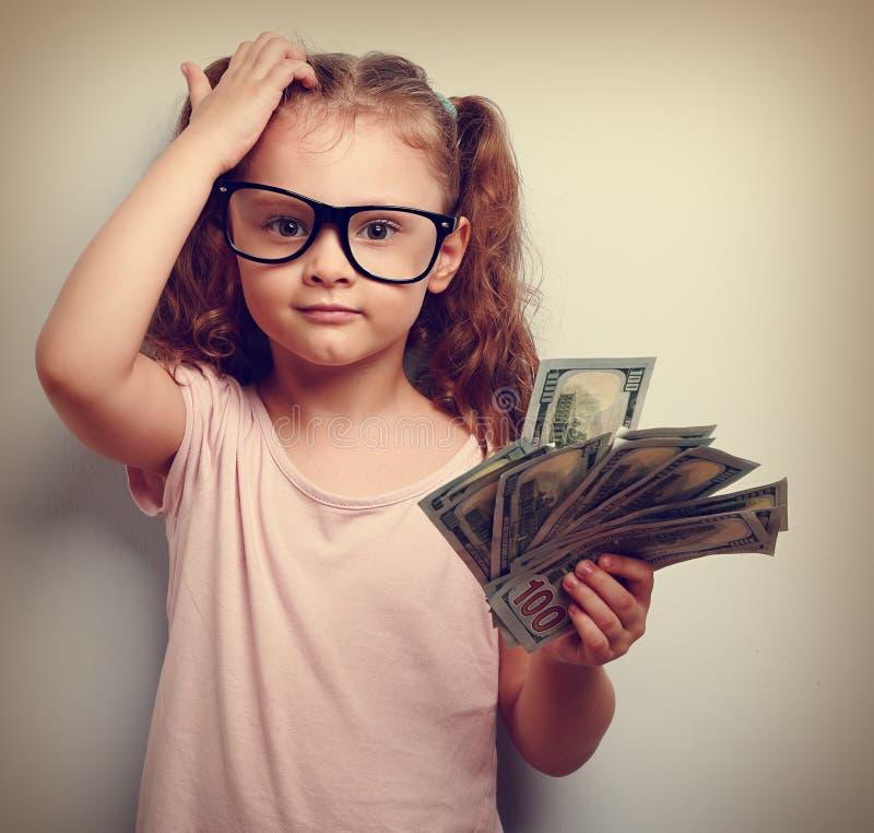Kleiner Professor in den Augengläsern, die den Kopf, Geld halten verkratzen stockfotografie