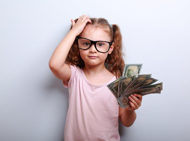 Kleiner Professor in den Augengläsern, die den Kopf, Geld halten verkratzen stockfoto