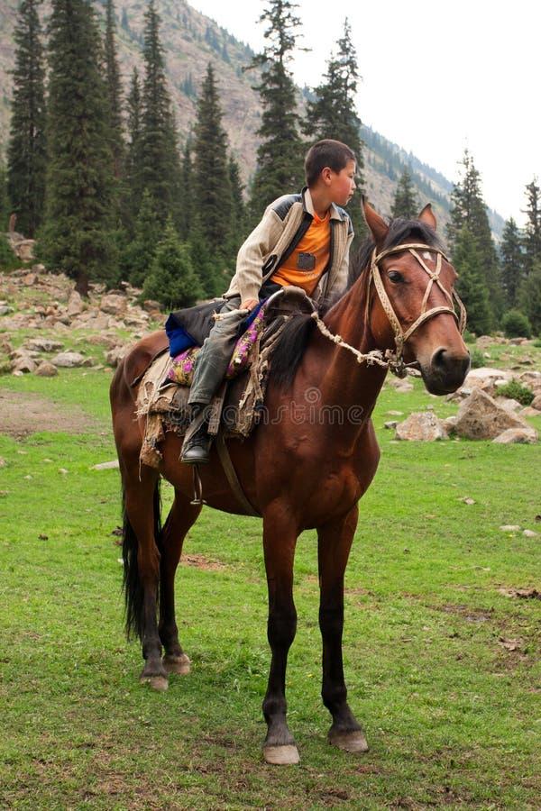 Kleiner Reiter, der auf einem braunen Pferd in einem Tal zwischen den Bergen von Zentralasien sitzt lizenzfreies stockfoto