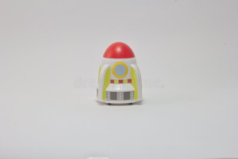 Kleiner roter Kopf des Weltraumraketespielzeugs auf einem weißen Hintergrund lizenzfreies stockbild
