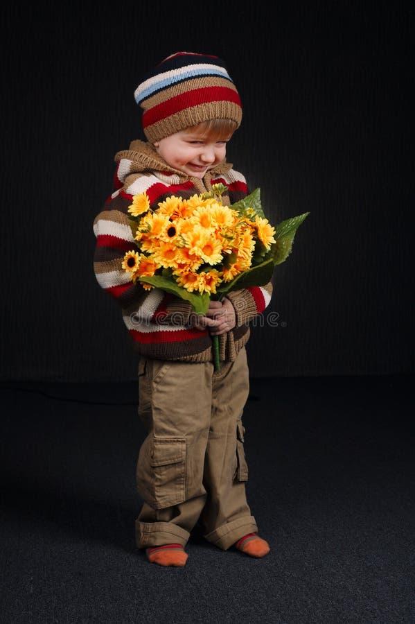 Kleiner süßer Junge mit Blumen lizenzfreies stockfoto