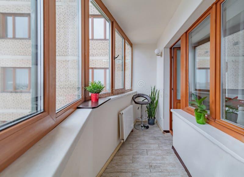 Kleiner sauberer, gemütlicher Balkon mit Fenster und Sessel lizenzfreie stockbilder