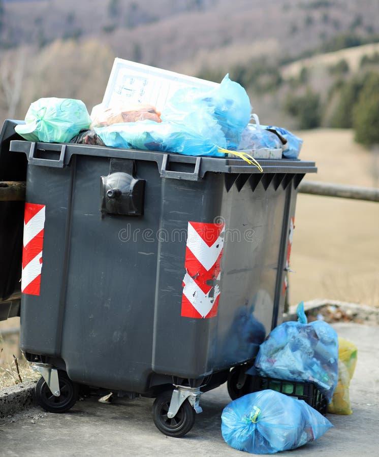 kleiner schwarzer Müllcontainer und viele Abfalltaschen stockfotos