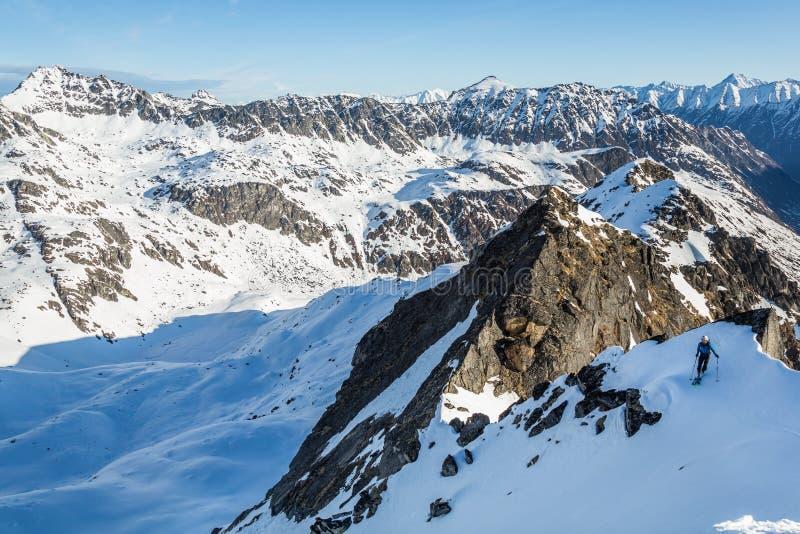 Kleiner Skifahrer, der in eine eisige Spitze über Gletschern und in Schnee in Fern-Alaska auf einem backcountry Skitour fällt stockbild