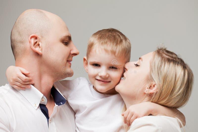 Kleiner Sohn des Mutter- und Vatikusses Junge ist in der Mitte und seine Eltern sind herum stockfotografie