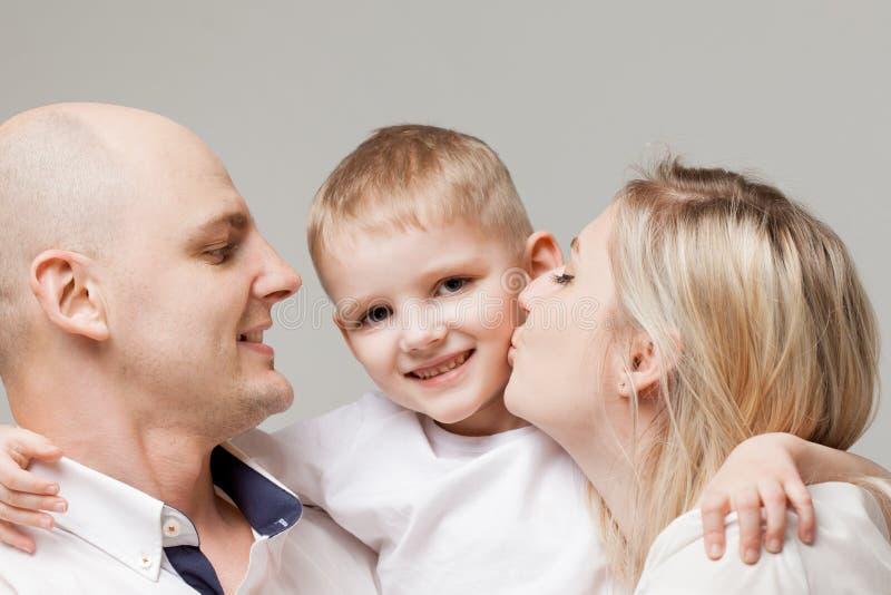 Kleiner Sohn des Mutter- und Vatikusses Junge ist in der Mitte und seine Eltern sind herum stockbilder
