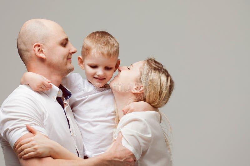 Kleiner Sohn des Mutter- und Vatikusses Junge ist in der Mitte und seine Eltern sind herum stockfoto