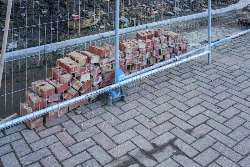 Kleiner Stapel von Ziegelsteinen, hinter dem Stahlfechten an der Baustelle stockfoto