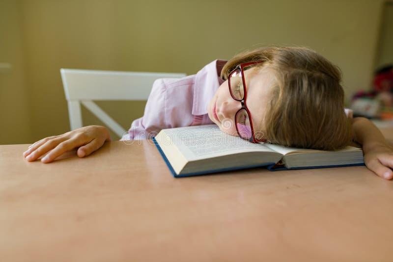 Kleiner Student in den Gläsern schläft an einem Schreibtisch, ihr Kopf auf einem offenen Buch Schule, Bildung, Wissen und Kinder lizenzfreie stockfotos