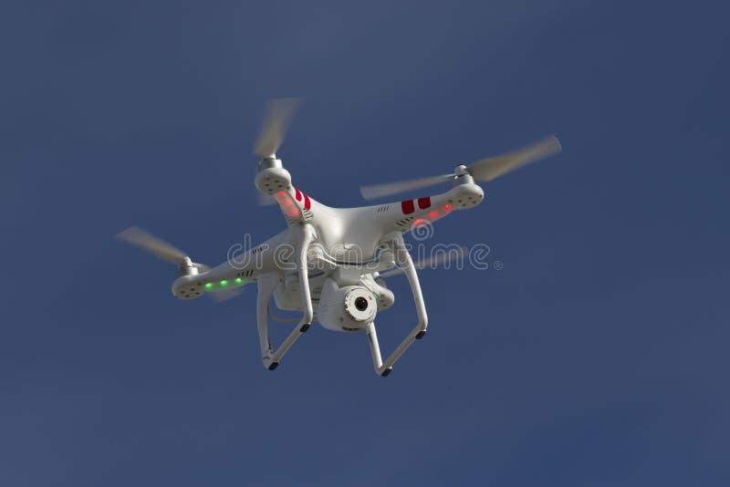 Kleiner unbemannter Hubschrauber mit einer Kamera, die in Himmel schwimmt lizenzfreies stockfoto