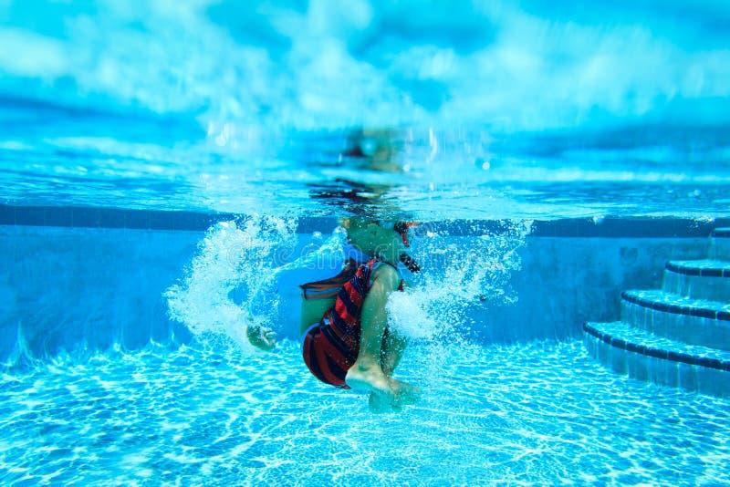 Kleiner Unterwasserjunge mit Maske im Swimmingpool stockbilder