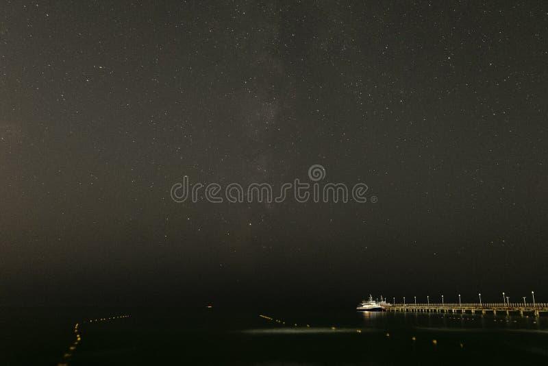 Kleiner Vergnügungsdampfer festgemacht zu einem Pier nahe dem sternenklaren nächtlichen Himmel der Seeküste über dem Meer lizenzfreies stockbild