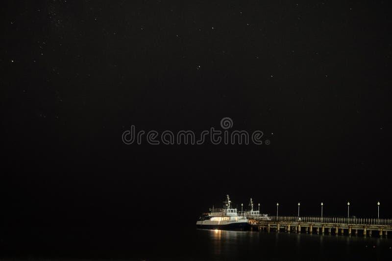 Kleiner Vergnügungsdampfer festgemacht zu einem Pier nahe dem sternenklaren nächtlichen Himmel der Seeküste über dem Meer stockfotos