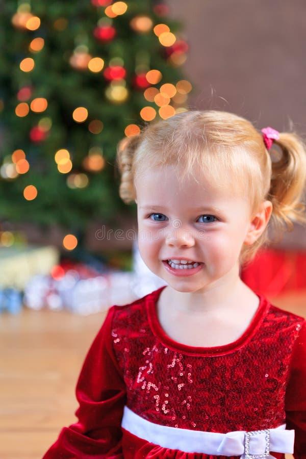 Kleiner Verlust Sankt, die vor dem Weihnachtsbaum lächelt lizenzfreies stockfoto