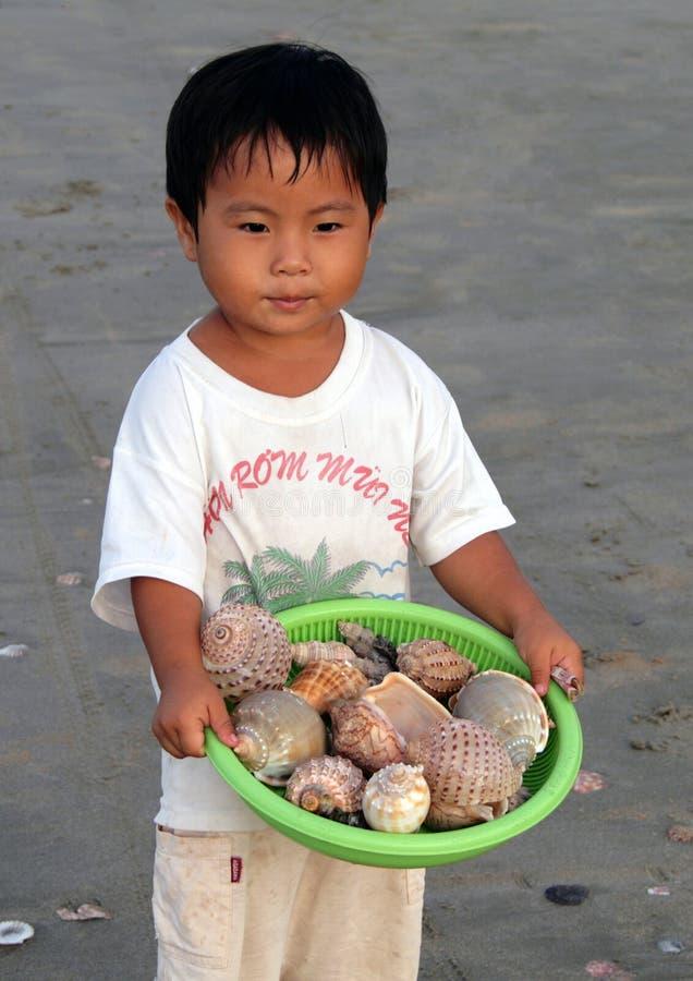 Kleiner vietnamesischer Junge, der Oberteile auf dem Strand verkauft stockbilder