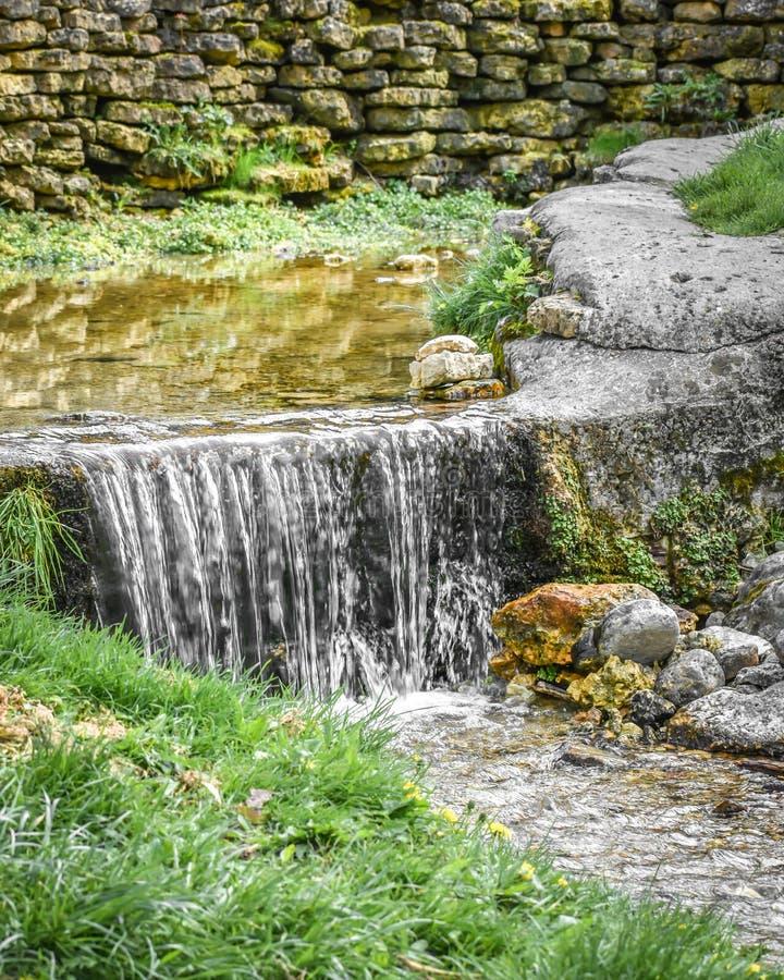 Kleiner Wasserfall mit Felsen-Wand lizenzfreie stockbilder