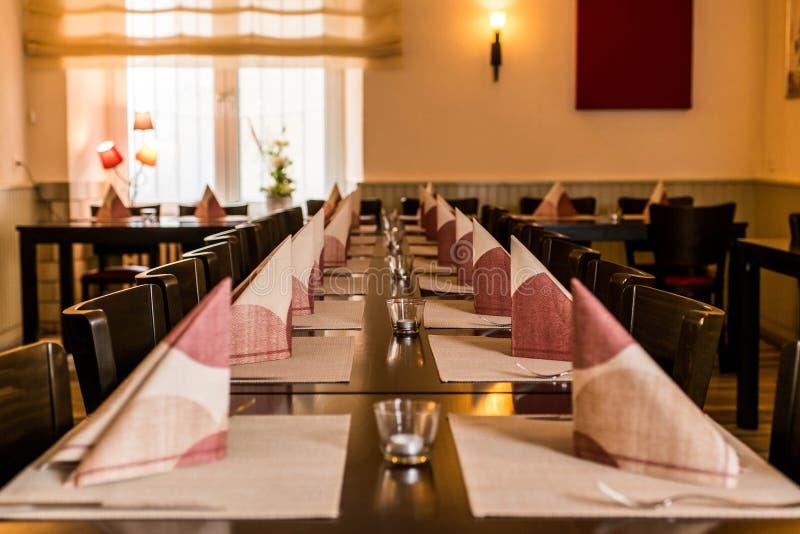 Kleiner weißer Teller und Schüssel auf hölzerner langer Tabelle bereiten sich für Abendessennachtparteirestaurant vor lizenzfreies stockbild