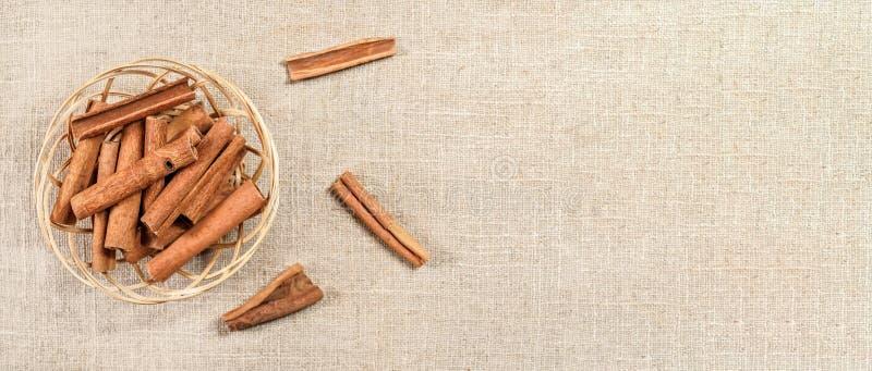 Kleiner Weidenkorb mit Zimtrindestöcken auf Leinentischdecke, Ansicht von oben Breiter Fahnenraum für Textrecht lizenzfreies stockbild