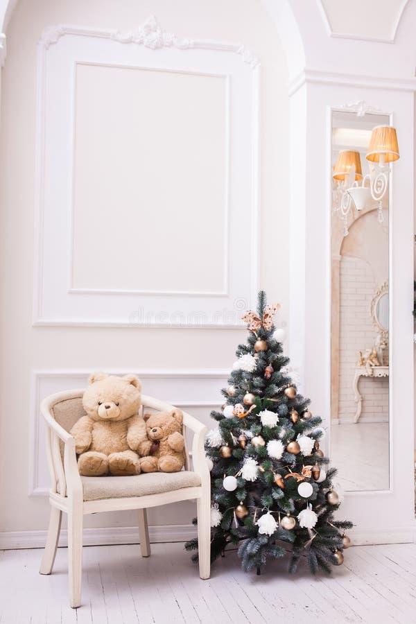 Kleiner Weihnachtsbaum nahe Stuhl mit Teddybären stockfoto