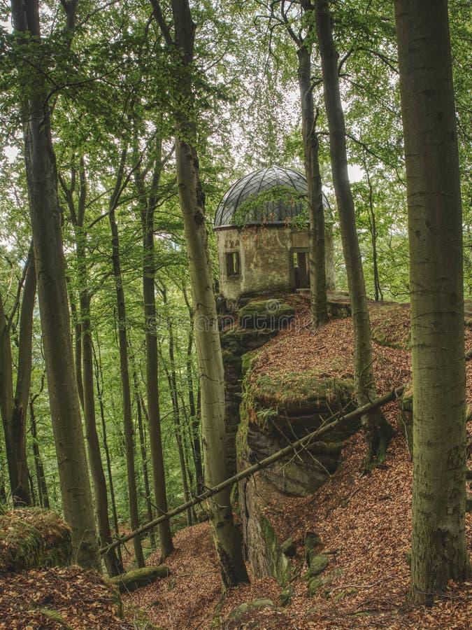 Kleiner Winterberg gazebo på en stenig kulle som döljas i bokträdskog arkivbild