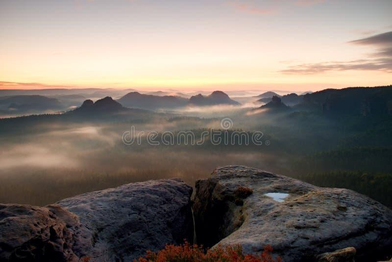 Kleiner Winterberg sikt Fantastisk drömlik soluppgång på överkanten av det steniga berget med sikten in i den dimmiga dalen arkivfoton