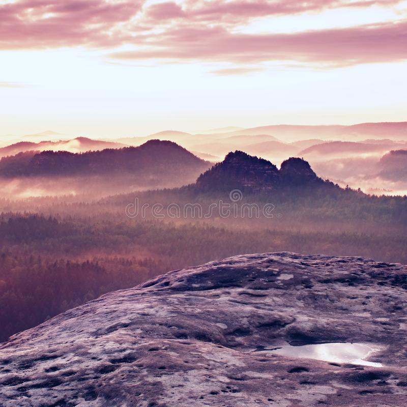 Kleiner Winterberg sikt Fantastisk drömlik soluppgång på överkanten av det steniga berget med sikten in i den dimmiga dalen royaltyfri bild