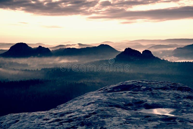 Kleiner Winterberg sikt Fantastisk drömlik soluppgång på överkanten av det steniga berget med sikten in i den dimmiga dalen arkivbild